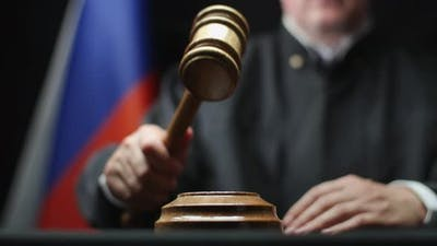 Judge Hammering With Wooden Gavel Against Russian Flag In Court Room