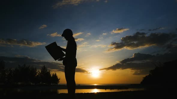 Silhouette Female Traveler at Sunset. The Girl Looks at the Map and Looking for a Path on a