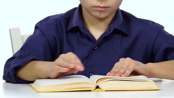 Thumbnail for Boy Sits at the Table Leafing Through the Pages of a Book. White Background. Close Up