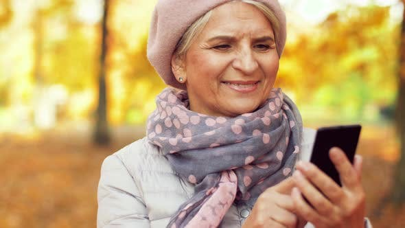 Thumbnail for Happy Senior Woman with Smartphone at Autumn Park 13