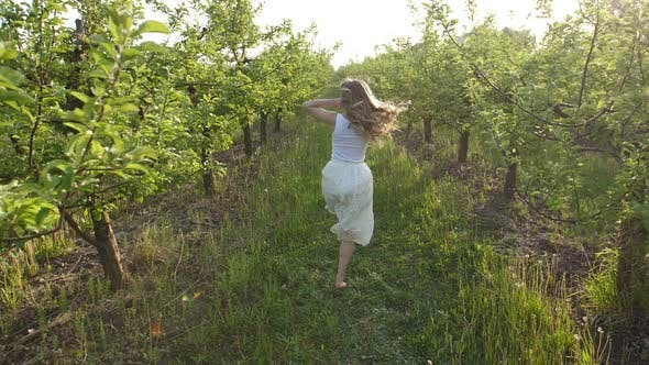 Thumbnail for Woman with Flying Hair Running in Spring Orchard