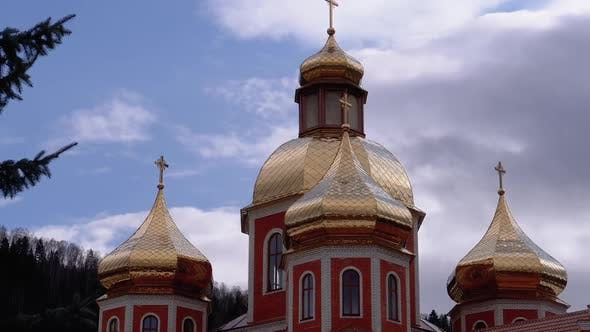 Ukrainian Church with Golden Domes Against the Sky and Clouds in the Carpathian Mountains
