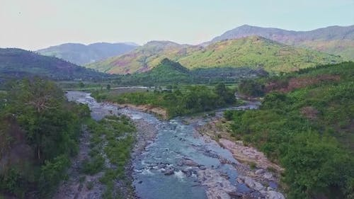 Drone Flies Over River Near Road Against Tropical Lands