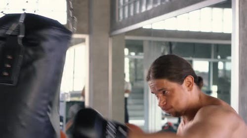 Strong Man Punching Boxing Bag