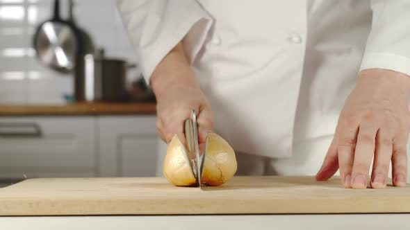 Thumbnail for Chef Chopping A Head Of Onion On Wooden Board While Cooking