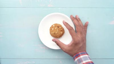 Hand Pick Whole Meal Cookies on Wooden Background