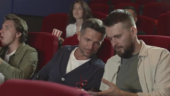 Thumbnail for Two Male Friends Using Smartphone in the Cinema