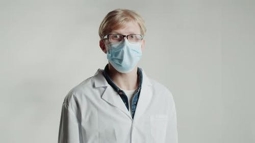 Caucasian Strict Man Doctor in Medical Mask Looking in Camera on White Background Shaking His Finger