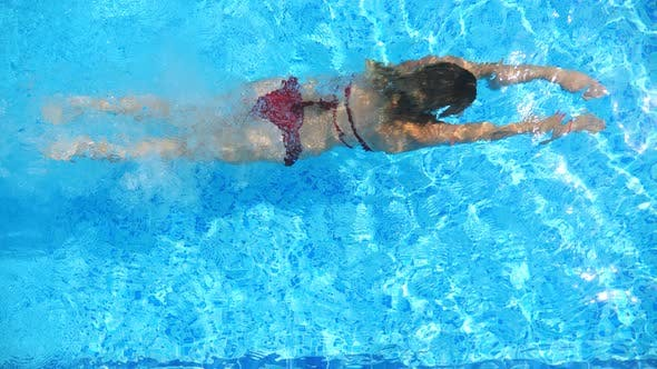 Thumbnail for Woman in Red Bikini Diving in Pool and Splashing Crystal Clear Water. Sexy Girl Swimming Under Water