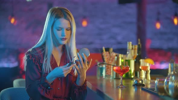 Thumbnail for Gorgeous Young Woman Sitting By the Bartender Stand and Applying Red Lipstick on Her Lips
