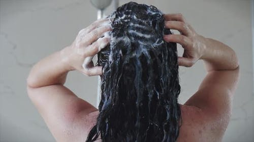 Pretty Young Girl Washes Away the Shampoo From Her Hair While Standing Under a Warm Shower Stream