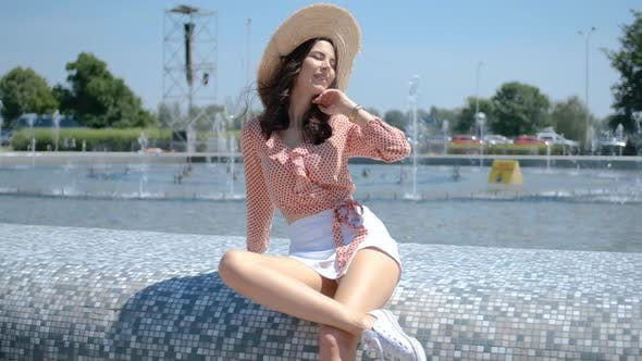 Thumbnail for Beautiful Woman Posing Next To City Fountain in Summer Time