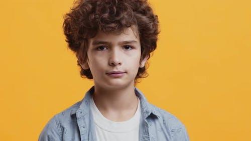 Adorable Boy Smiling at Camera, Studio Portrait Over Orange Background