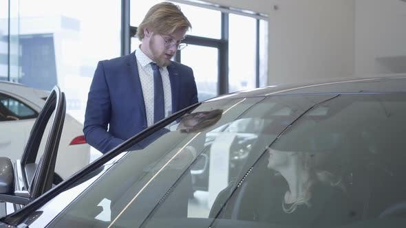 Cover Image for Handsome Young Car Salesman Discussing New Automobile Model in Motor Show. Car Dealership