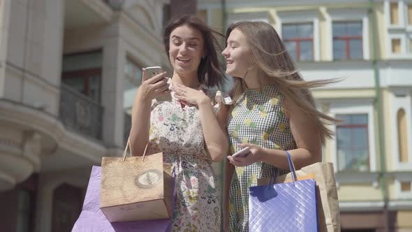 Thumbnail for Two Happy Girlfriends After Shopping with Shopping Bags Texting on the Cellphone