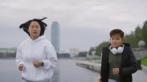 Thumbnail for Asian Mother and Son Running Along Riverside in City