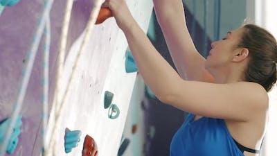 Beautiful Lady Climbing in Sports Center Ejoying Rock-climbing Alone Indoors