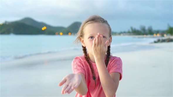 Thumbnail for Adorable Little Girl at Beach Having a Lot of Fun at Sunset. Happy Kid Looking at Camera and Kissing