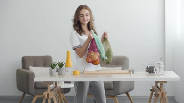 Thumbnail for Young Smiling Woman Putting Bags with Fruit and Vegetables on the Table in Modern Office