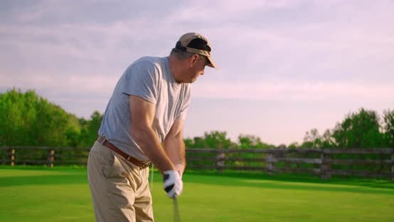 Thumbnail for Handsome Older Golfer Swinging and Hitting Golf Ball on Beautiful Course at Sunset.