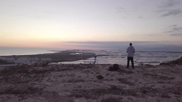 Thumbnail for Aerial View Of Man With A Camera On Top Of A Cliff looking the sunset