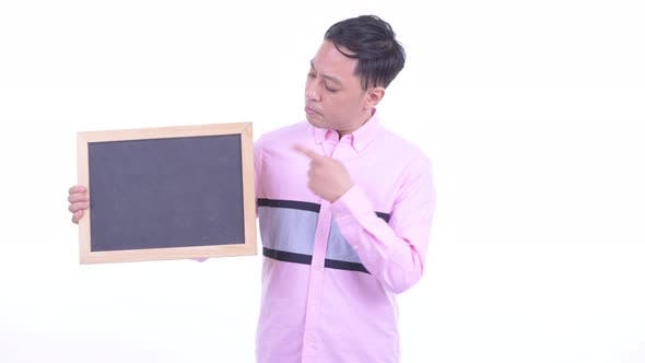 Thumbnail for Stressed Japanese Businessman Holding Blackboard and Giving Thumbs Down