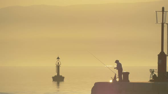 A fisherman on a quay at sunset