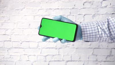 Hand in Latex Gloves Holding Smart Phone with Green Screen