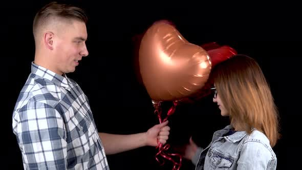 Thumbnail for A Young Man Gives a Young Woman Heart-shaped Balloons. Man and Woman Kissed on a Black Background
