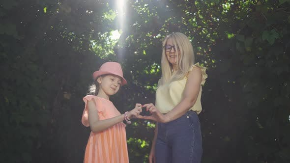 Thumbnail for Cute Mature Blond Mother and Her Pretty Daughter Making Heart Shape with Their Fingers in the Summer