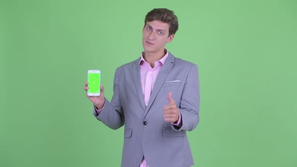 Thumbnail for Happy Young Businessman Showing Phone and Giving Thumbs Up
