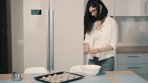 Young Woman Making Homemade Cookies in Kitchen