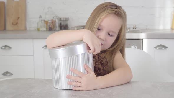 Thumbnail for Nahaufnahme Porträt von schönen kaukasischen Mädchen öffnen grauen Geschenk-Box und Blick ins Innere. Niedliches Kind
