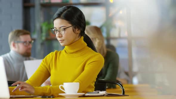 Thumbnail for Young Asian Business Lady Typing on Laptop at Coffeeshop Table