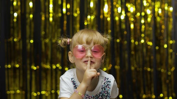 Child Girl Putting Finger on Lips Making Silence Gesture, Asking To Keep Secret. Shh. Be Quite.
