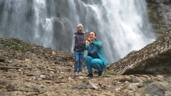 Woman with Daughter Taking Selfie By a Waterfall