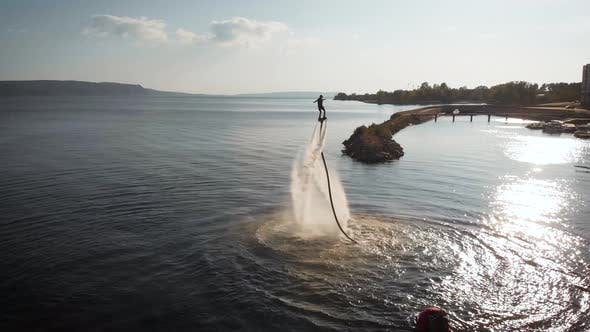 Thumbnail for Male Acrobat Is Flying on Flyboard on Sea in Summer Day, Performing Trick, Aerial View, Hydroflight