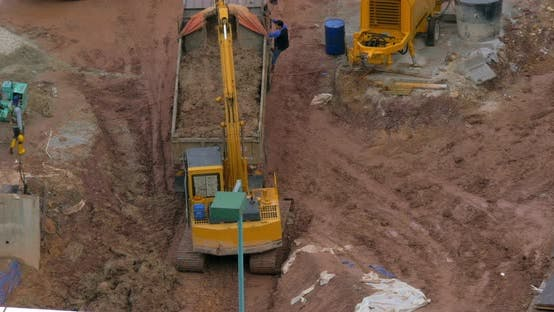 In Kuala Lumpur, Malaysia in the Pit Excavator Pours Earth Into a Truck
