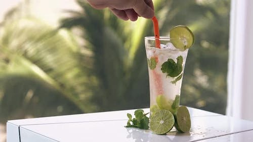 Man Stirs Soft Mojito Drink with Plastic Straw on Big Table