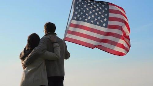 Famille patriotique avec un grand drapeau de l'Amérique en plein air