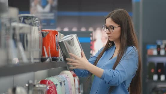 Thumbnail for Young Beautiful Brunette Woman Chooses an Electric Kettle To Buy. Inspects the Device, Examines the