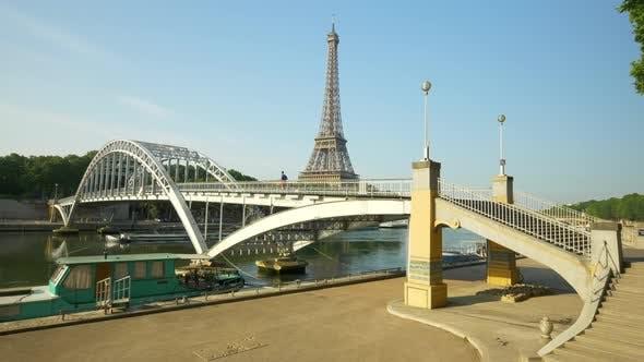 A man running across a bridge with the Eiffel Tower.