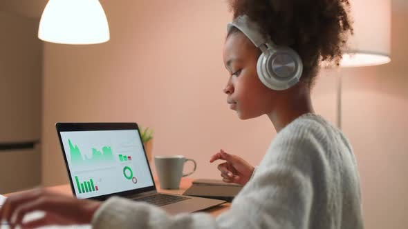 Young African Girl is Learning to Work with Financial Statistics on a Remote Work at Home Working