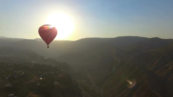 Thumbnail for Aerial View of Hot Air Balloon Flying Over Mountain Village at Beautiful Sunset