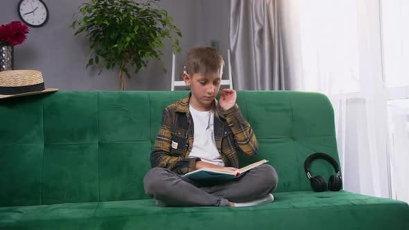Thumbnail for Teen Boy is Tired to Read Uninteresting Book, Sitting on Green Soft Couch at Home