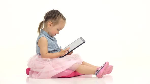 Thumbnail for Little Girl in Her Hands Is Holding Aipad. White Background