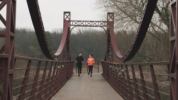 Thumbnail for Sportive young woman and man are jogging across pedestrian bridge, Running concept