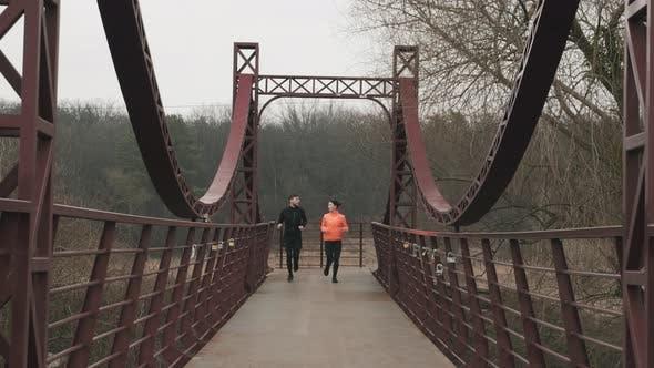 Thumbnail for Sportliche junge Frau und Mann joggen über die Fußgängerbrücke, Laufkonzept