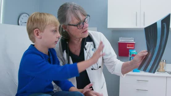 Female senior pediatrician showing x-ray of hand to child patient