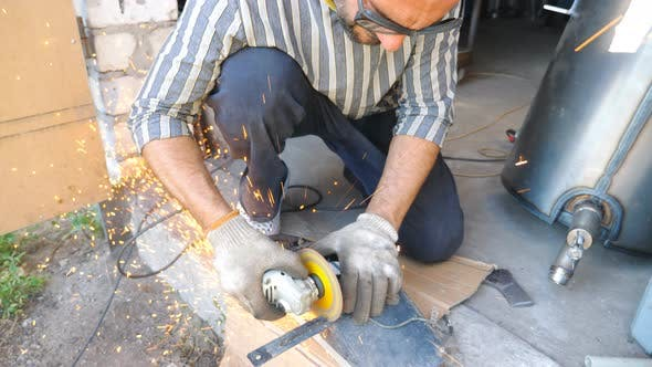 Thumbnail for Adult Repairman or Mechanic Grinding Metal Using Circular Saw. Worker Cutting Some Detail in Garage